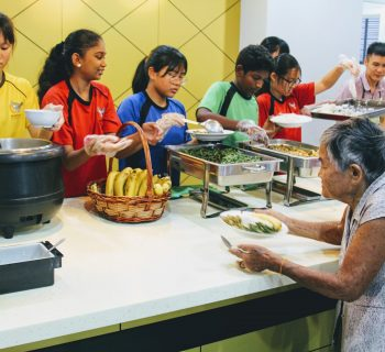 International School KL students distributing food to old folks at charity centre